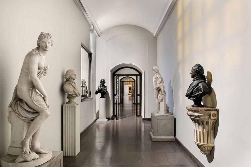 Korridorformat museisal med skulpturer och byster i vitt och svart längst med väggarna.