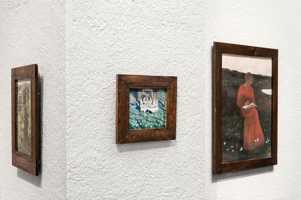 Närbild på tre mindre målningar i träram mot vit vägg.