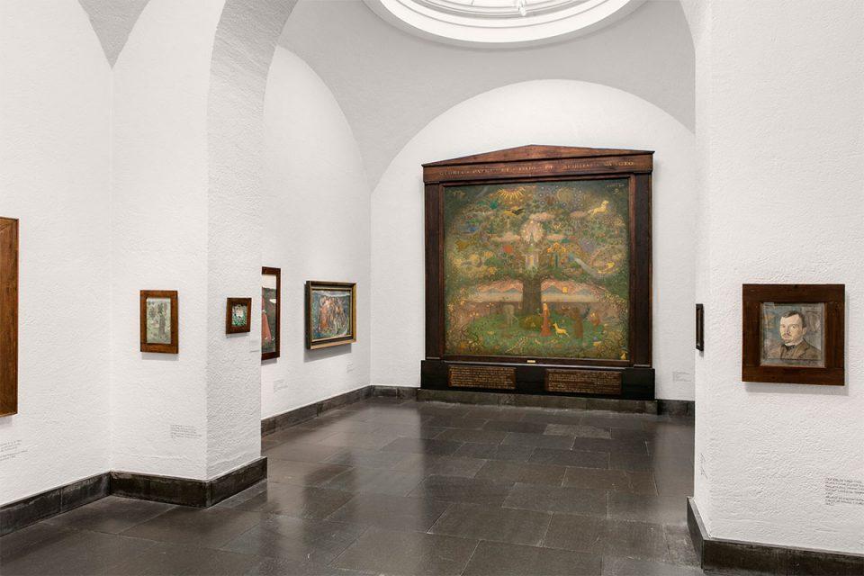 Museisal med välvt tak och målningar på väggar. I fonden en stor målning i träinramning föreställande