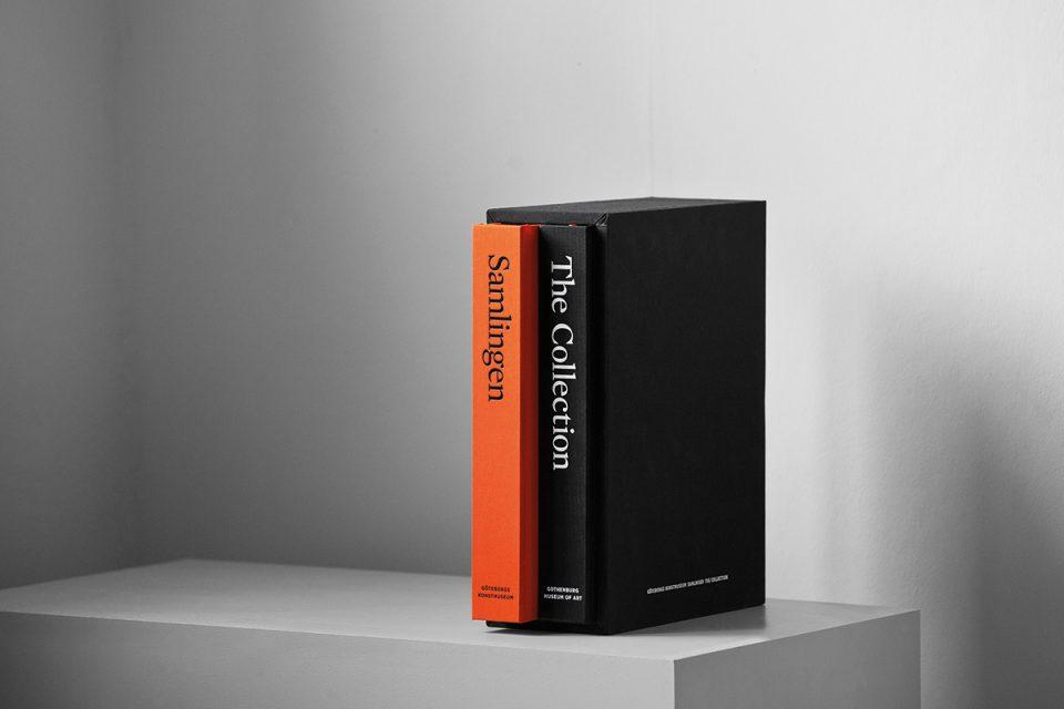 Två stora bokryggar ståendes intill varandra. Den ena svart, den andra orange.