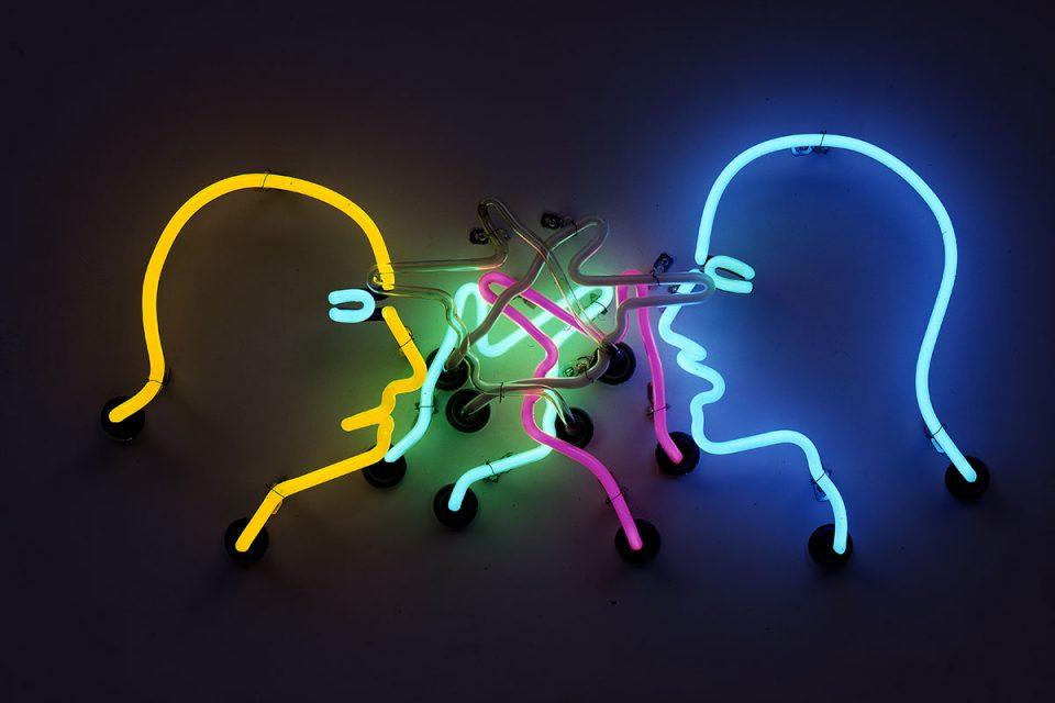 Neonskylt med färgade siluetter mot mörk bakgrund av två ansikten riktade mitt emot varandra