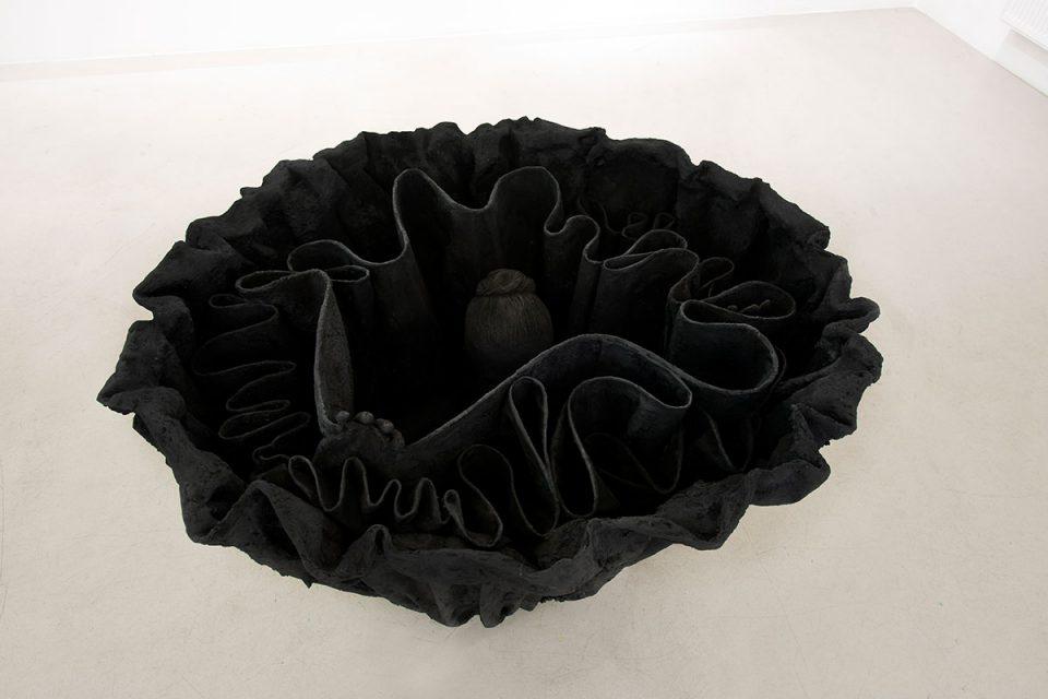 Fotografi av svart skulptur mot vit bakgrund föreställandes en uppochnervänd volangkjol som ett kvinnohuvud och hand syns inuti.
