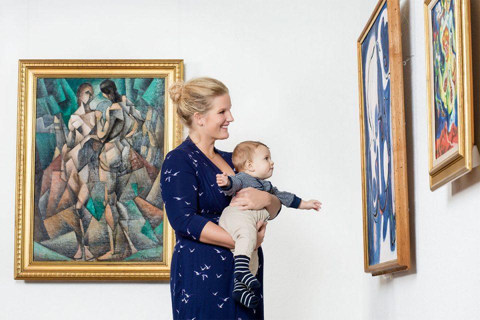 Kvinna i blå klänning med barn i famnen som tittar på målningar i museisal.