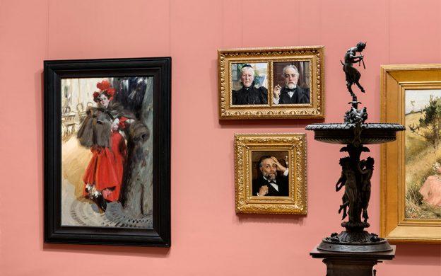 Tre tavlor på rosa vägg, två små porträtt av paret Fürstenerg, en större målning av kvinna med röd klänning i stadsmiljö.