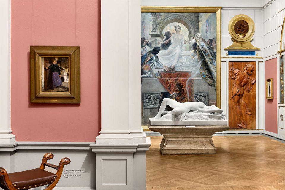 Museisal med flera olika konstverk. Det finns målningar, en skulptur och träreliefer.