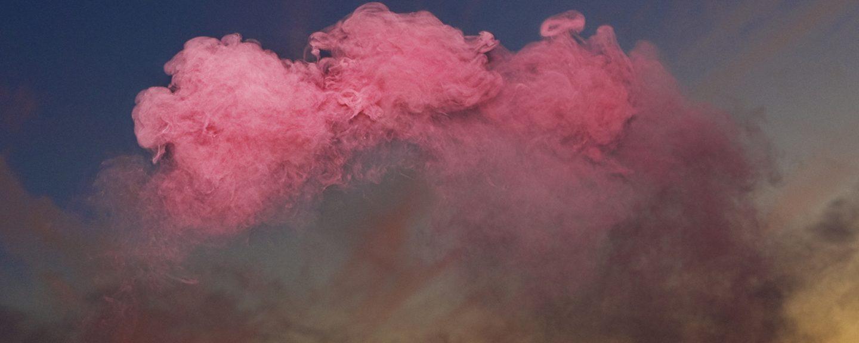 Vy av landskap med karga berg, himmel som skiftar från organe till blå med kraftigt rosa moln högst upp.