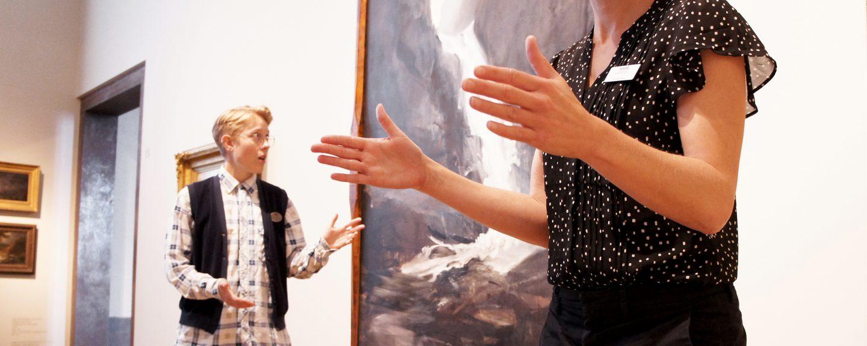 En konstpedagog och en teckenspråkstolk står framför en målning i en museisal.