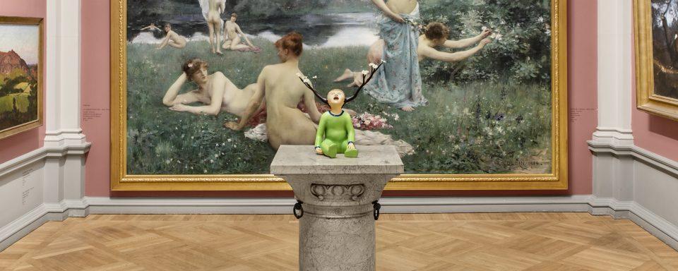 Skulptur av barn i grön dräkt med blomstrande grenar från huvudet, framför en målning med nakna kvinnor på en äng.