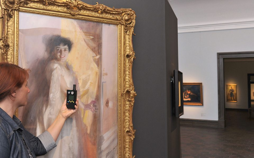 En konservator mäter ljusnivån framför en större målning av en kvinna i ljus klänning