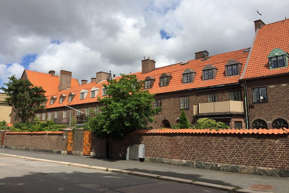 Fasadlänga i brunt tegel, rött tegeltak och mur i samma material framför.
