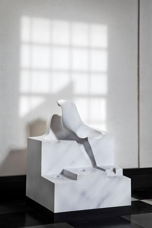 Stor skulptur i vit marmor, som har kantiga former och avtryck av två sittande personers kroppar.
