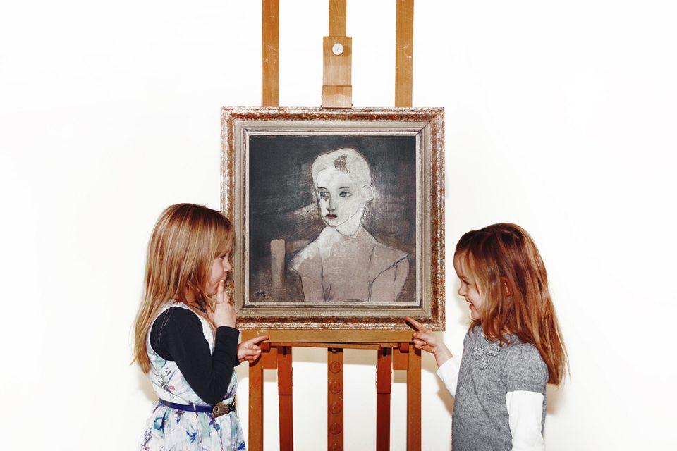 Två barn i profil som tittar på en porträttmålning. De pekar på den och ser glada ut.