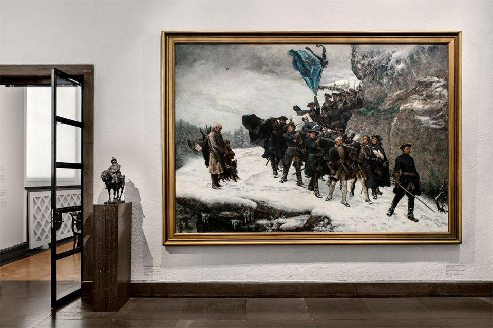 Museisal med målning av Karl XIIs likfärd där ett tiotal män tågar på snöig väg intill klippor.