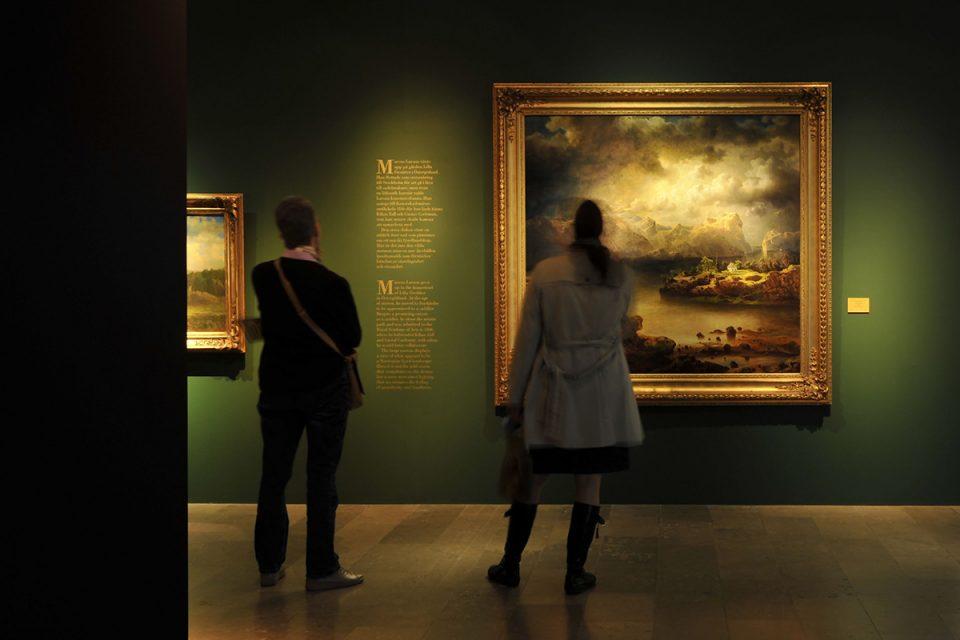 Museirum med mörkt gröna väggar, två stora landskapsmålningar och ryggar på två besökare.