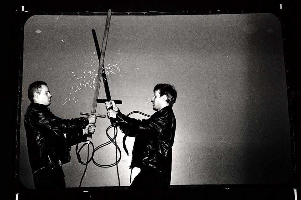 Svartvit foto av två personer som håller i varsitt metallsvärd som vertikalt slår emot varandra