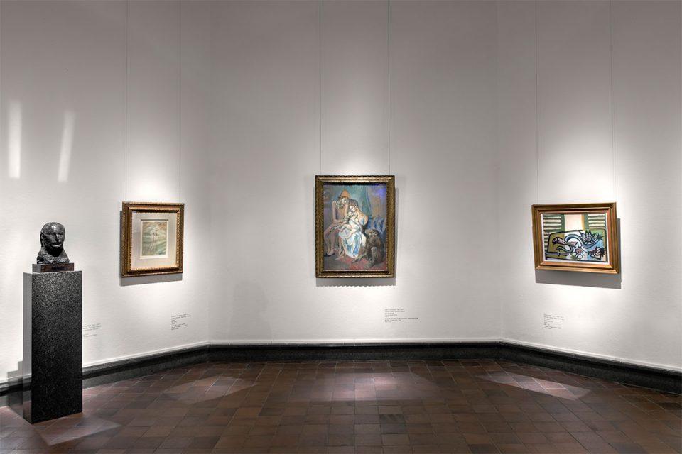 Museisal med tre målningar på vägg av Pablo Picasso, en mindre skulptur på pidestal till vänster.