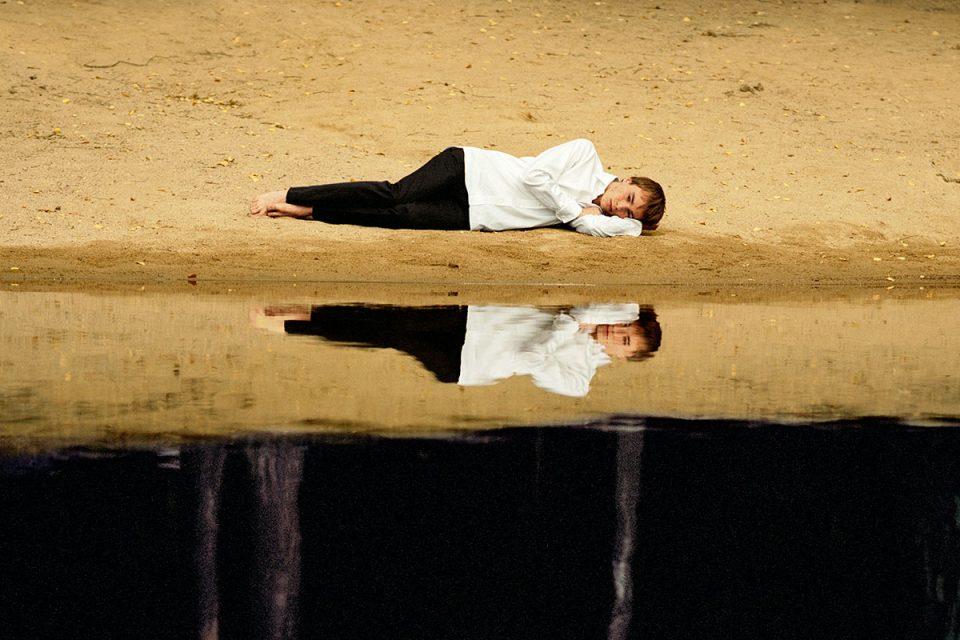 Person i vit skjorta och svarta byxor ligger på sandstrand. En horisontell linje skär igenom bilden, där personen och stranden speglas i vatten i bildens nedre del. Vattnet reflekterar även en svart himmel.