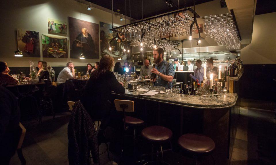 Interiör av restaurang Mr P. Bardisk rakt fram, höga stolar och bord längs väggarna.