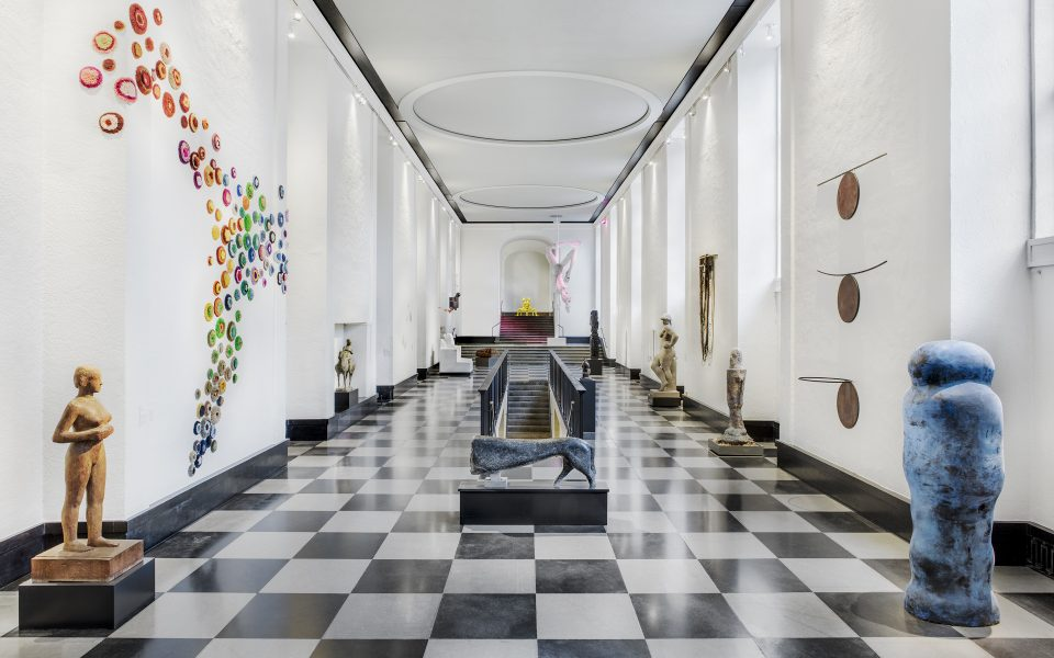 Stor hall med vita väggar och tack, schackrutemönstrat golv. Skulpturer placerade längs väggarna.