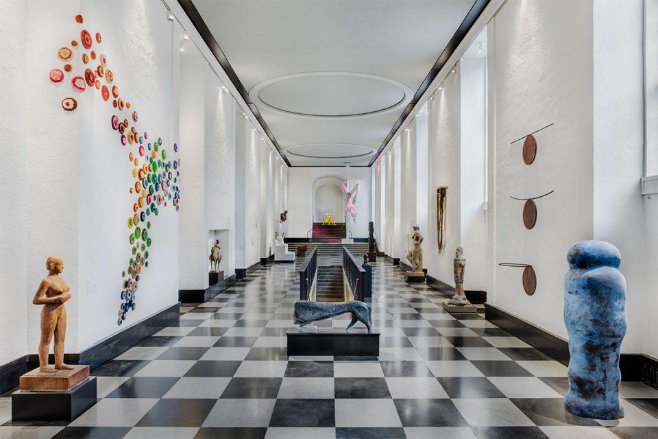 Översikt av Skulpturhallen centrerad vy. Svartvit rutigt golv, trapp till nedre plan i mitten och konstverk placerade på golv och väggar.