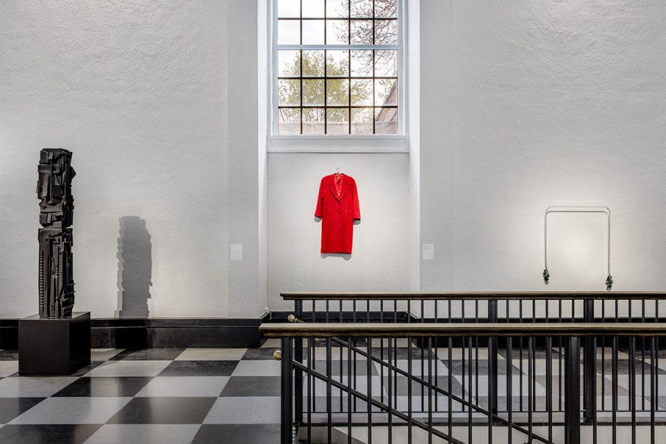 Skulpturhallen, svartvitrutigt golv, svart trappräcke. Konstverk i form av röd kappa hänger rakt fram på vägg under fönster med spröjs.