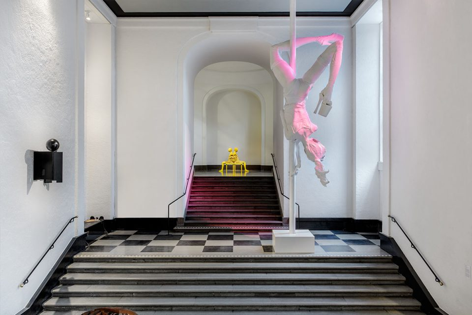 Skulpturhallen - centrerad trappa med två avsatser. Två stora skulpturer på varje avsats. Båda föreställande människokroppar. En i vit en i gul.