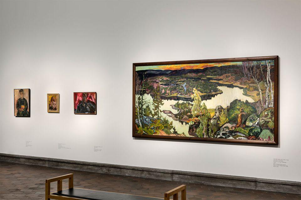 Museisal med en stor målning av landskap med träd och sjö i fågelperspektiv.