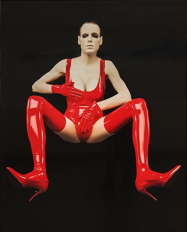 Foto av nutida androgyn person i röd läderbody och högklackade stövlar, mot svart bakgrund.