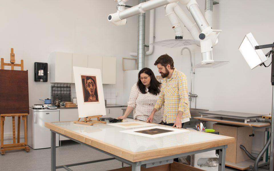 Kvinnlig konservator visar manlig kollega arbetet med verk på papper i konservatorateljén.