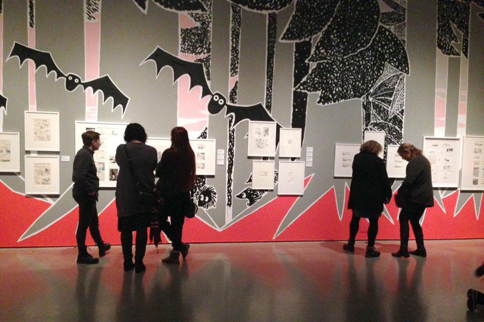 Utställningsrum med väggmålning i grått, vitt, rött och rosa. Människor betraktar tavlor på väggarna.