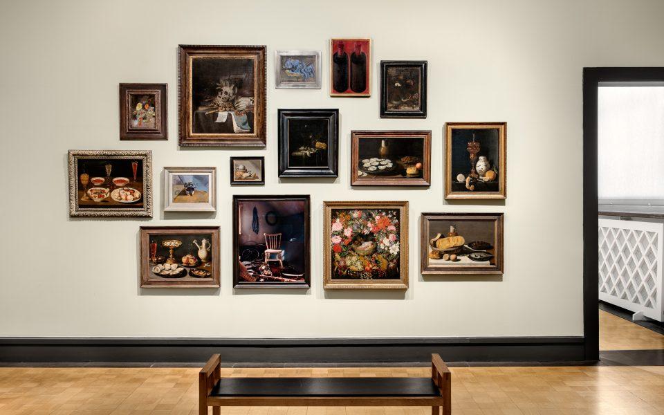Vägg i museisal med ett tiotal stillebenmålningar på vägg rakt fram.