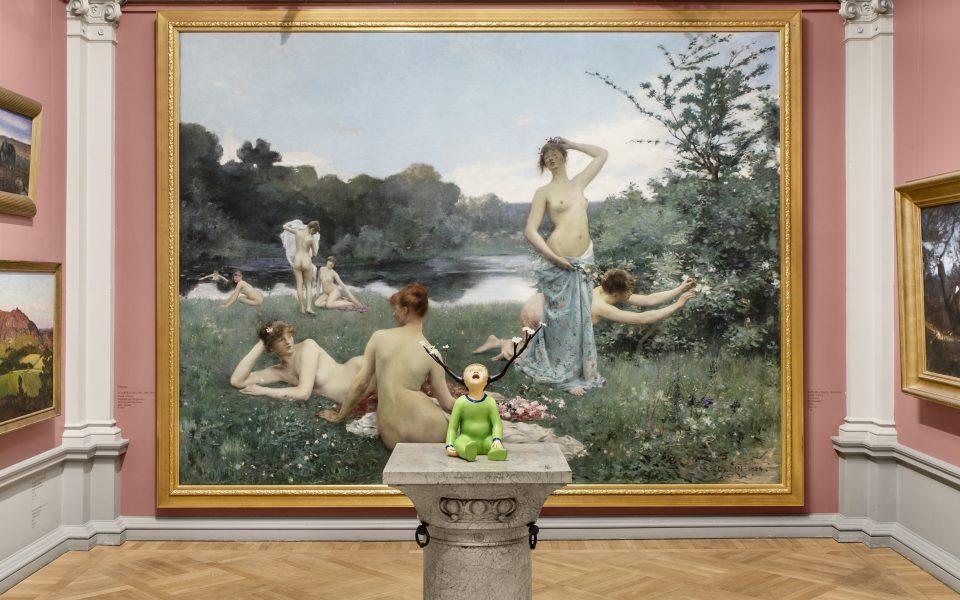 Museisal med rosa väggar, stor målning av nakna kvinnor i gräs vid vatten. Skulptur framför föreställandes barn i grön dräkt med grenar från huvudet.