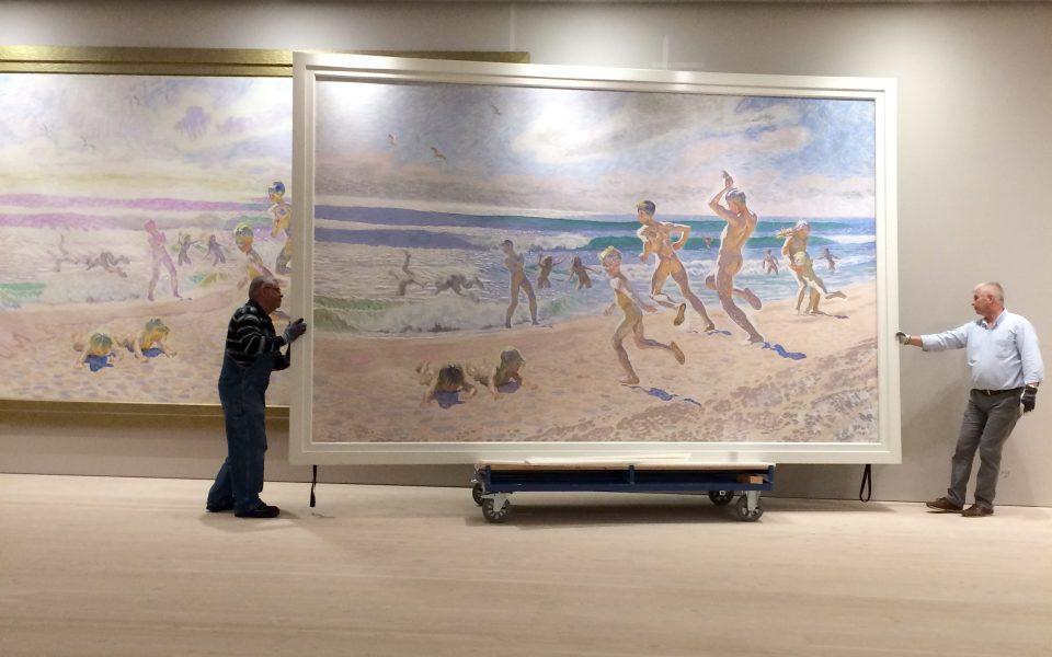 Museirum där två personer bär in en väldigt stor målning föreställandes personer som springer i vattnet på sandstrand.