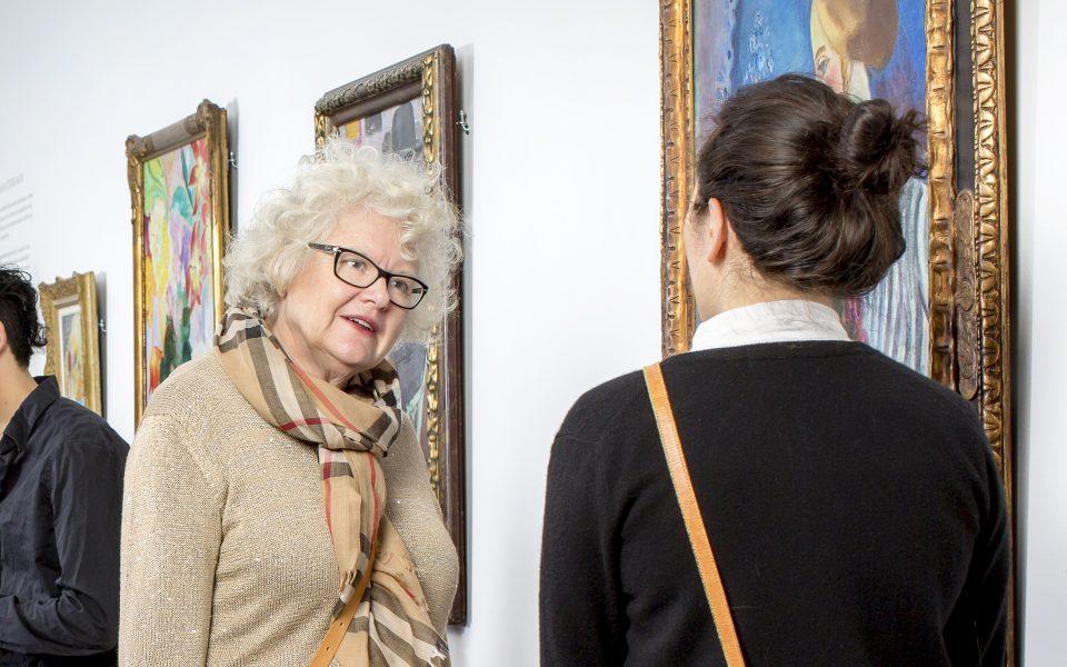 Foto av två kvinnor som pratar med varandra i en museisal med stora målningar på väggarna.
