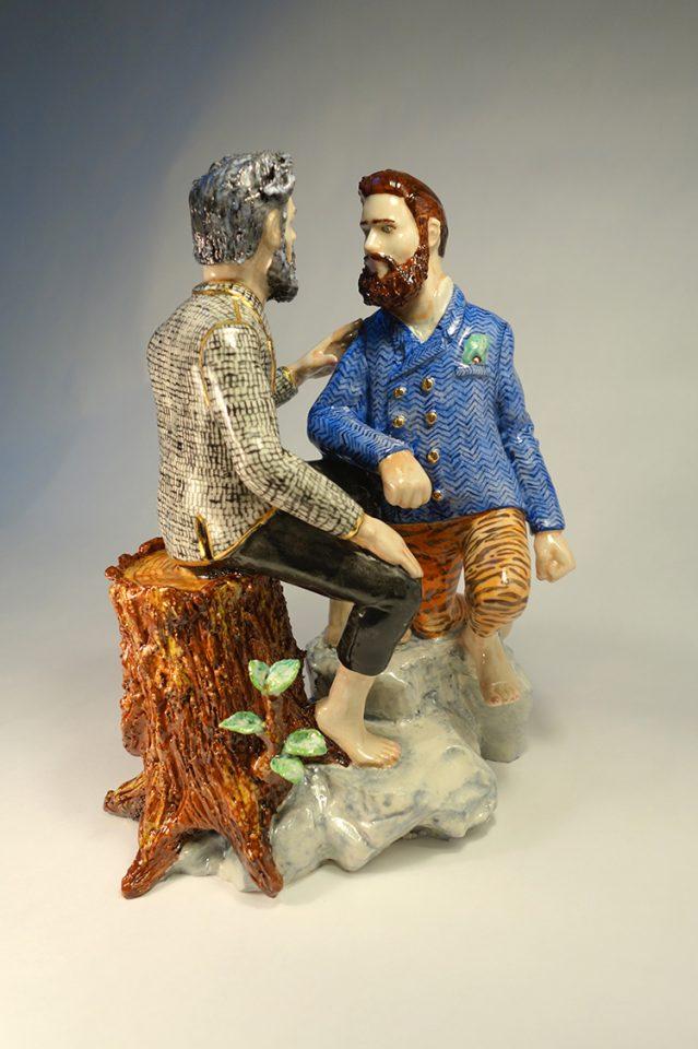Modern figurin i porslin föreställandes två män i hipsterstil som är vända mot varandra på ett intimt sätt.