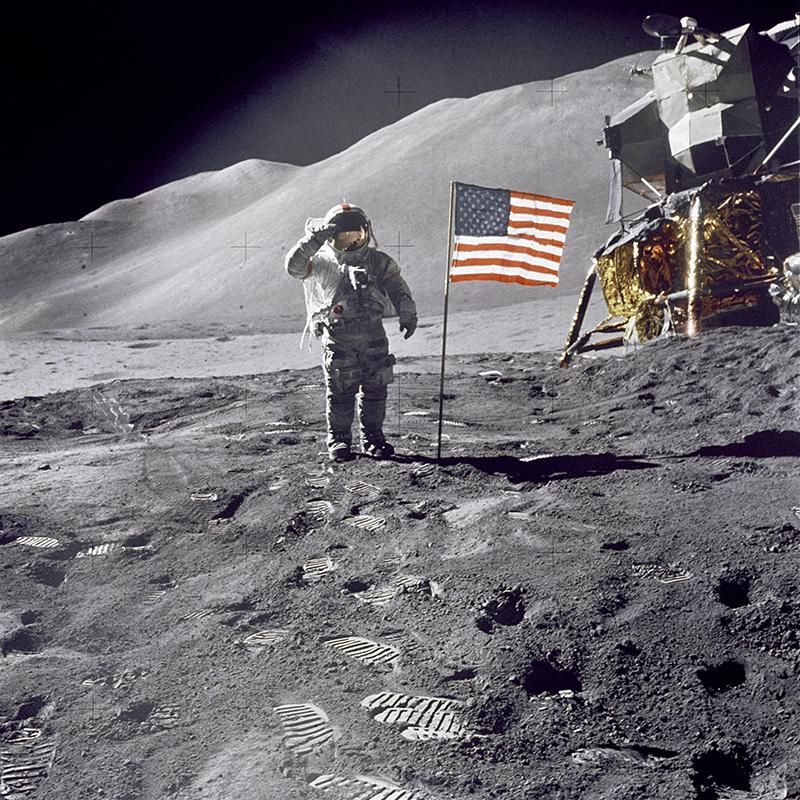 Person i rymddräckt gör honnör vid amerikanska flaggan på månen
