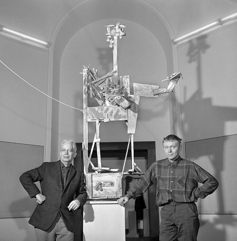 Svartvit foto på två män som tittar mot kameran. Bakom den står en stor modell.
