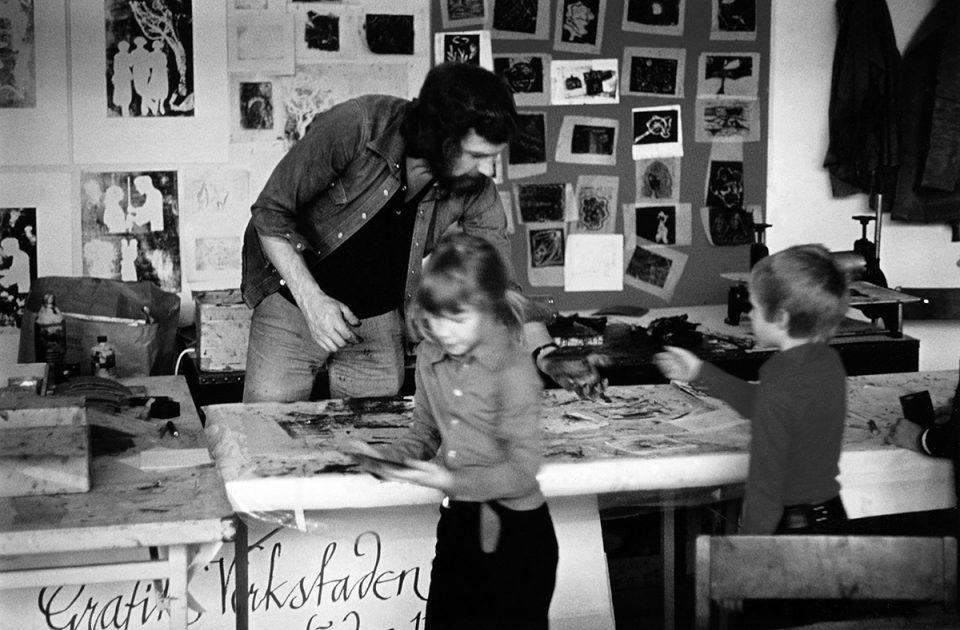 Svartvit foto från grafiverkstad med en man och två barn