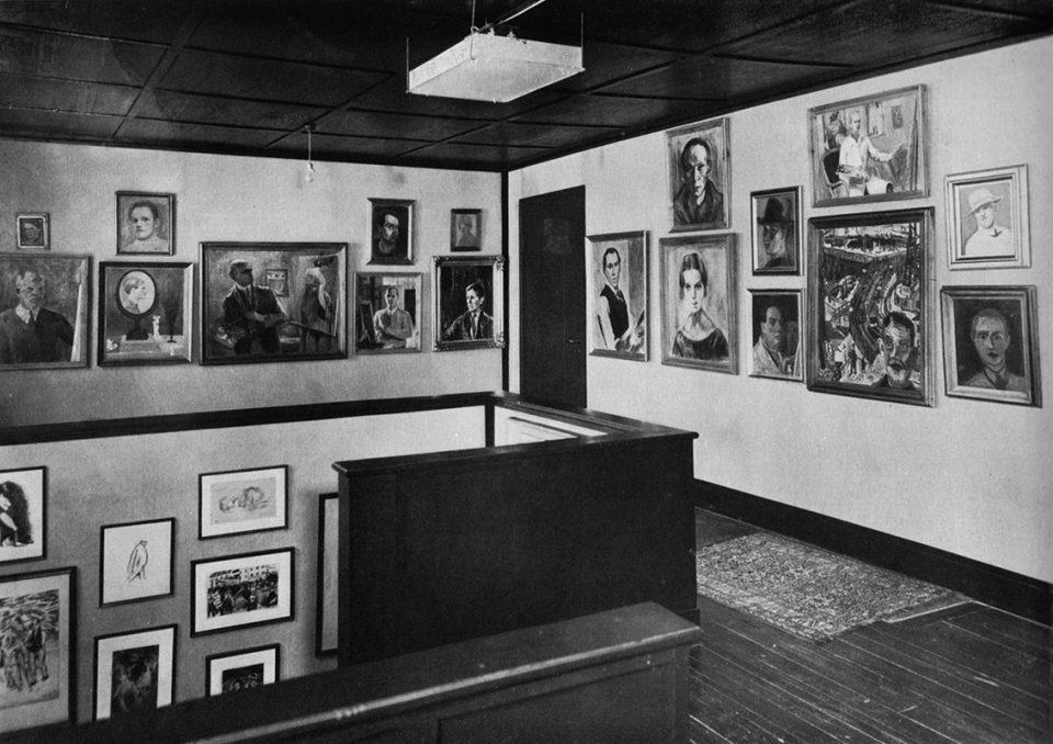 Svartvit foto av självporträttsamling i hemmiljö från tidigt 1900-tal