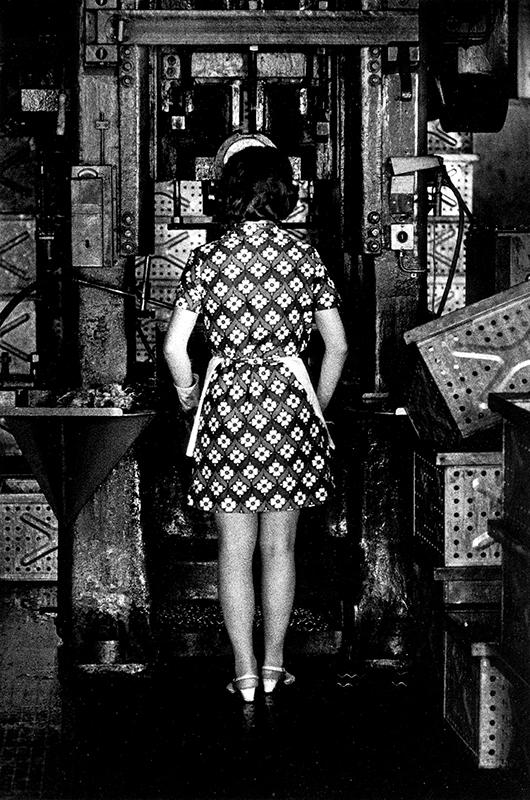 Svatvit foto av kvinna i mönstrad klänning med ryggen vänd mot kameran.