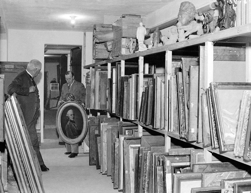 Svartvit foto av två män i magasin med målningar. Den ena håller upp en porträttmålning.