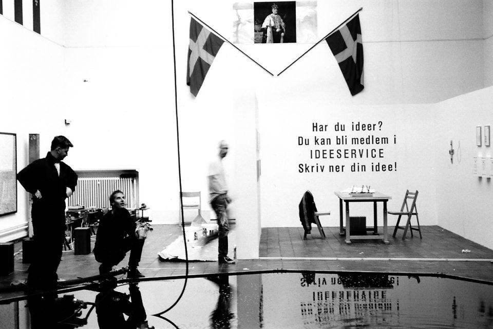 Svartvit foto av utställnings hall med vita väggar, en vattenspegel på golvet.