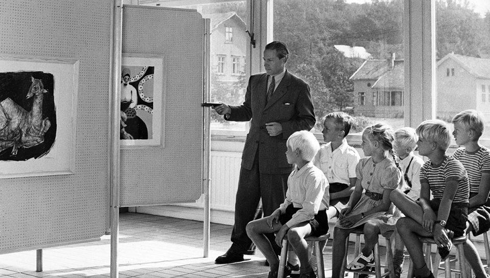 Svartivit foto från 1950 där man i kostym visar målning på skärmvägg för grupp av barn.
