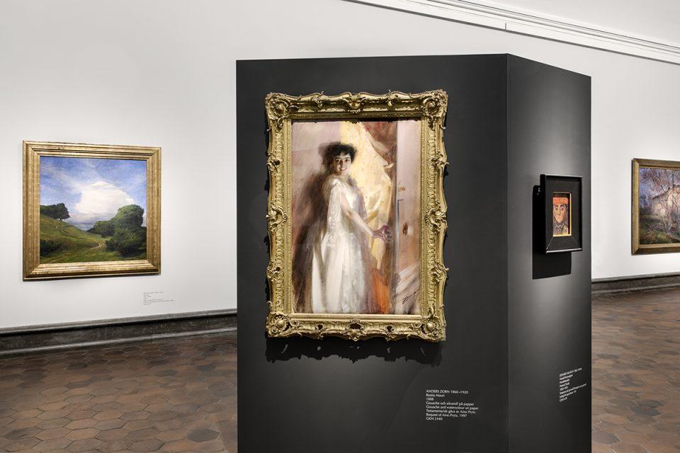 Översikt av museisal med målningar i guldram på vägg.