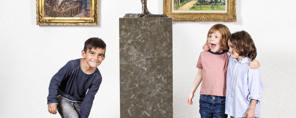 Tre glada pojkar som står vid en pidestal i en museisal.